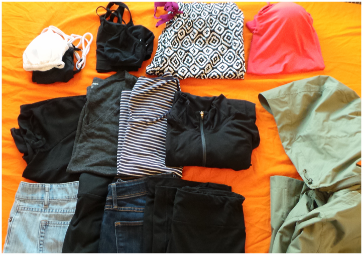 First Row (left to right): Bikini set, sports bra and lightweight bra, sleeping pants, sleep top Second Row (left to right): black silk short-sleeve top, grey cotton short-sleeve v-neck, tri-quarter striped top, long-sleeve activewear top Third Row (left to right): mid-length jeans shorts, black mid-length compressions, dark wash denim jeans, black yoga pants Also pictured on the far right is a long waterproof rain coat *Not pictured: 10 pairs of underwear