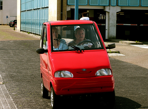 These are the tiny 'Canta' cars manufactured in the Netherlands and driven in bicycle lanes. I have since learned from its Wikipedia page that it was originally manufactured specifically as a mobility aid, for instance drivers with wheelchairs, to aid in commuting - - that's pretty awesome. Image source: http://onlytruecars.com/gallery/canta-lx.html