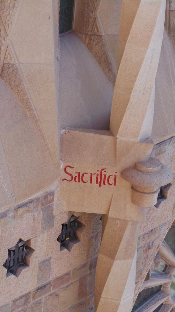 'Sacrifici' or 'Sacrifice' text on the Sagrada Familia exterior